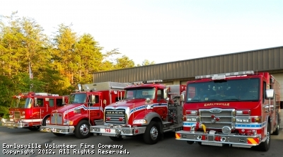 Picture of front of Earlysville Volunteer Fire Department with 4 emergency vehicles emerging from bays